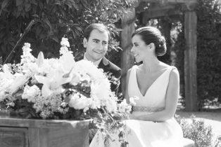 Fotografía en blanco y negro de los dos novios durante la celebración de la boda se sonrien