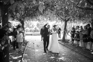 Fotografía en blanco y negro de lls novios bajo una lluvia de arroz despues de la celebración de la boda