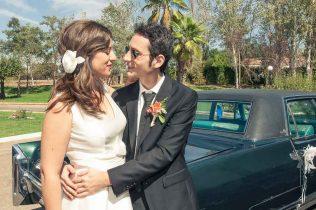 Pareja abrazada momentos antes de la boda junto al coche en el que ha llegado la novia