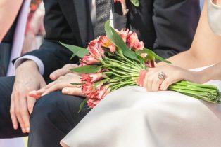 Detalle de las manos de los novios y el ramo durante la boda