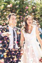 Los novios tras la boda bajo una lluvia de confetti de colores
